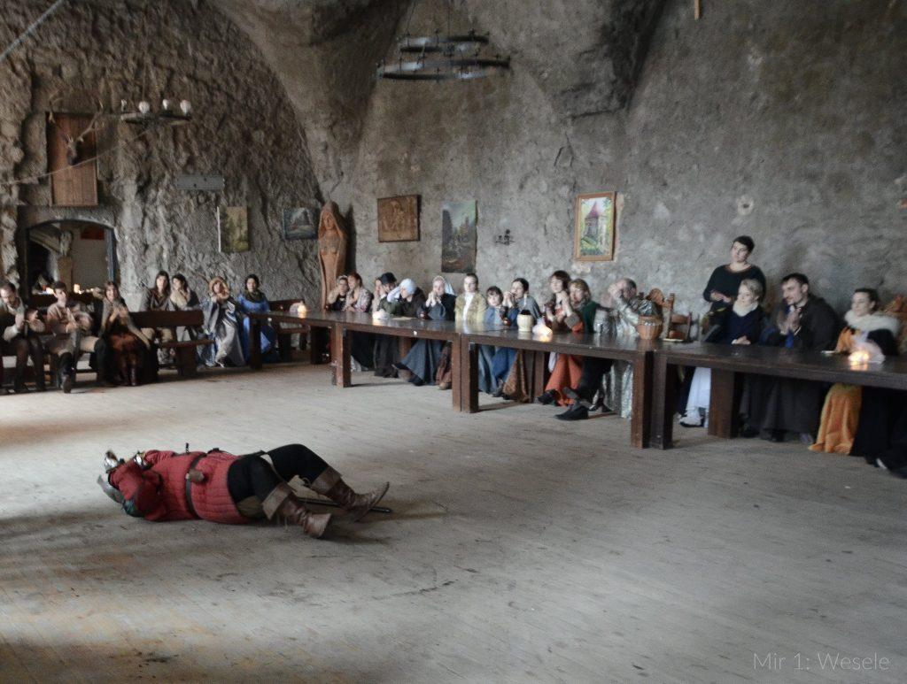 Martwa lub ranna postać pośrodku pełnej ludzi sali