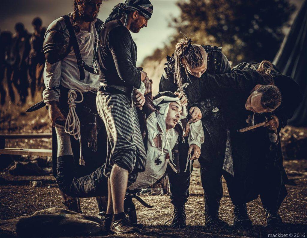 Grupa wojowników niesie rannego jeńca