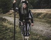 Znużony żołnierz z halabardą na krawędzi drogi
