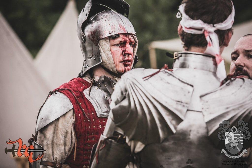 Żołnierz w saladzie z zakrwawioną twarzą rozmawia z innymi